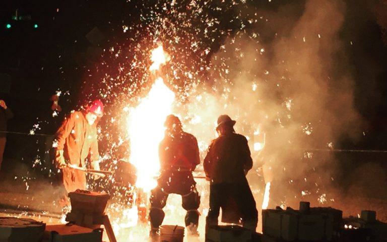 People pour iron into a forge with sparks flying.
